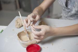 flicka gör leksak från lera foto