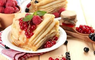 läckra pannkakor med bär, sylt och honung på träbord foto