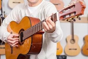 man spelar en gitarr i musikaffär foto