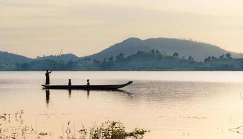 ede kvinnor som roddar dugoutbåt på sjön vid soluppgången