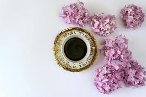 kopp kaffe, på vit bakgrund med blommor, foto