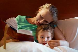 ung mamma som läser för sitt barn i sängen