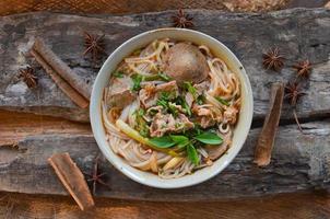 pho vietnamesisk nötköttsoppa på trä bakgrund foto