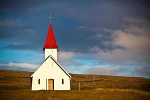 typisk lantlig isländsk kyrka under en blå sommarhimmel
