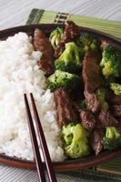 asiatisk nötkött med broccoli och ris närbild. vertikal foto