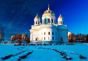 vit ortodox kyrka med guldkupoler mot blå vinterhimmel