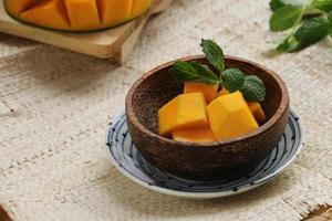 söta aromatiska mangobitar i kokosnötskalskålen foto