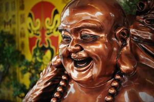 brons budai staty eller den lyckliga buddha foto