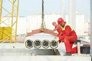 byggnadsarbetare som installerar betongplatta foto