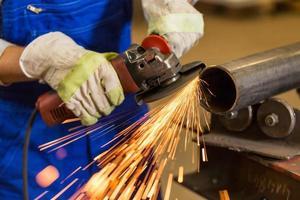 arbetare skär stål med vinkelslipare foto