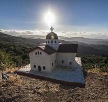 traditionell grekisk liten kyrka nära vägen foto