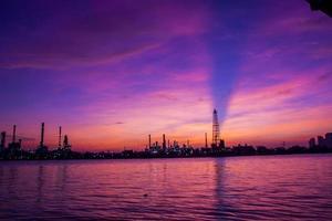 Panorama oljeraffinaderi längs floden i skymningen (Bangkok, Thailand foto