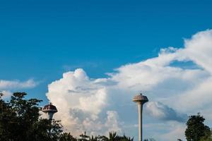 två vattentank torn på en molnig himmel foto