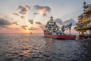leveransbåt vid solnedgång foto