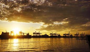 hamnlager med containerfrakt och kranbro foto
