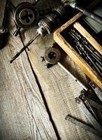 gammal borr, en låda med borrar, tång och linjal på foto