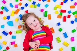 liten flicka som leker med färgglada block foto