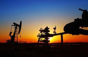 oljeledning och pumpenhet i silhuetten foto