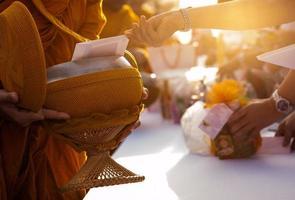 munk som tar emot mat och saker som erbjuds från människor foto