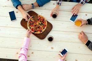 händer människor trä kafé pizza bord dricker mat elektroniska prylar foto