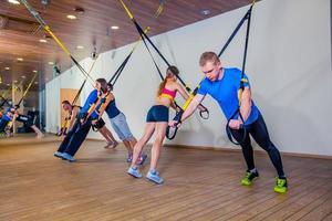 folk gör fitnesövningar med ett band i gymmet foto