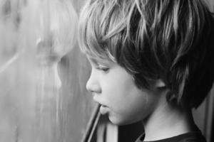 söt pojke tittar genom fönstret foto