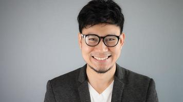 asiatisk affärsman i svart kostym med grå bakgrund. foto