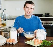 leende man matlagning ägg foto