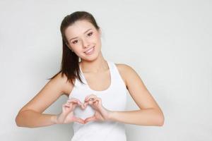studio skott av ung attraktiv flicka visar hjärta foto