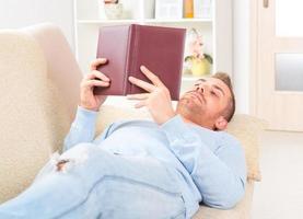 ung man läser bok foto