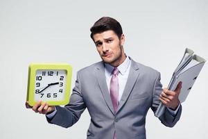 olycklig affärsman som håller mappar och klocka foto