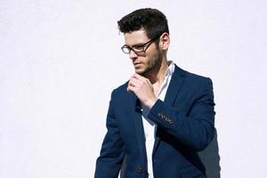 ung stilig man som bär modeglasögon mot neutral bakgrund med foto
