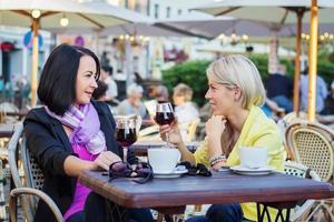 två kvinnor som har vänlig chatt på café foto