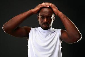 frustrerad afrikansk man som rör vid huvudet foto