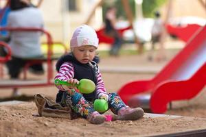 liten tjejlek med leksaker på sandlådan foto