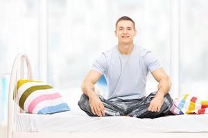 ung man i pyjamas som sitter på en säng foto