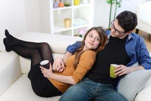 härliga par tittar på tv medan de dricker te i vardagsrummet foto
