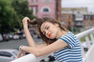 tjej lyssnar på musik i bakgrunden av en megacitet foto