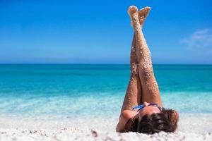 närbild av kvinnliga benbakgrund av det turkosa havet foto