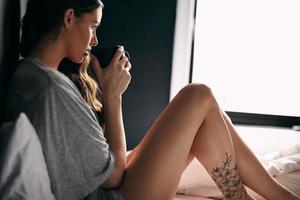 ung kvinna som dricker kaffe på sängen foto