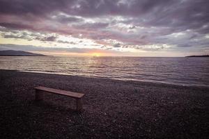 tom bänk på stranden vid solnedgången, tonad marsala foto