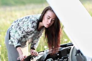 attraktiv brunett framför sin bil foto
