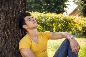 attraktiv ung man i park vilar mot träd foto