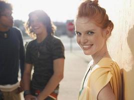 glad kvinna med manliga vänner i bakgrunden foto