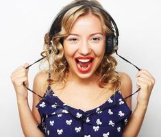 ung glad kvinna med hörlurar lyssnar musik