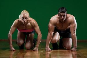 starka muskulösa par som knä på golvet
