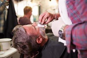 manlig frisör som förbereder klienten för rakning i butik foto