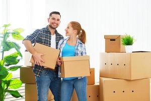 flyttar till en ny lägenhet. lyckliga par och kartong foto