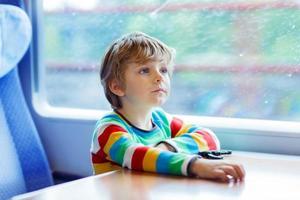 liten pojke som sitter i tåget och åker på semester foto