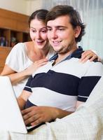 människor som sitter på soffan och surfar på internet foto